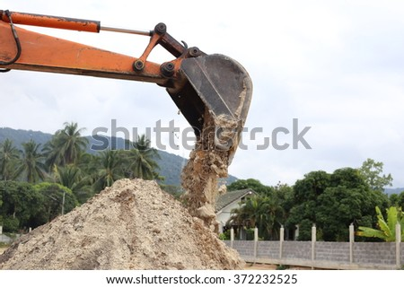 Working excavator backhoe opening shovel bucket to drop sand.