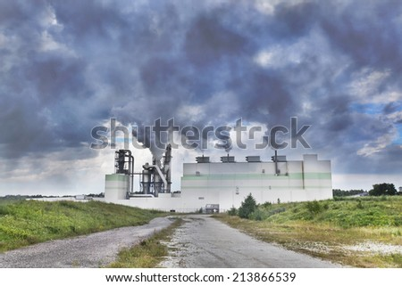 Working factory with huge columns of smoke above - stock photo