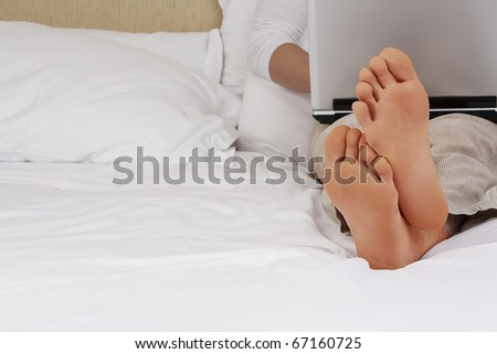 Working from home. Man relaxing in bed using laptop, close up on male foots. - stock photo