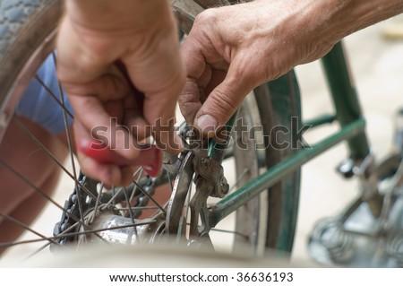 working hands repairing bicycle - stock photo