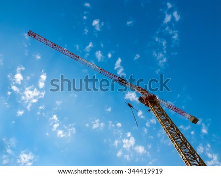 Working hoisting crane against blue sky with clouds. - stock photo