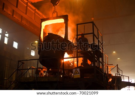 Working in a foundry. Red color is a reflection of the molten metal. - stock photo