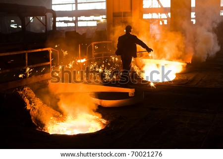 Working in a foundry. Workers looking down, red color is a reflection of the molten metal. - stock photo