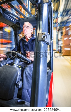 working in a warehouse on a forklift - stock photo