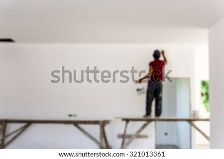 Working is painting (out of focus). - stock photo