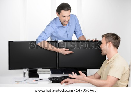 Working moments. Two young businessmen talking about business while one of them pointing computer monitor - stock photo