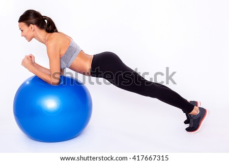 Working my upper body Full length portrait of a young woman doing exercise with a fitness ball and balancing over white isolated background. - stock photo