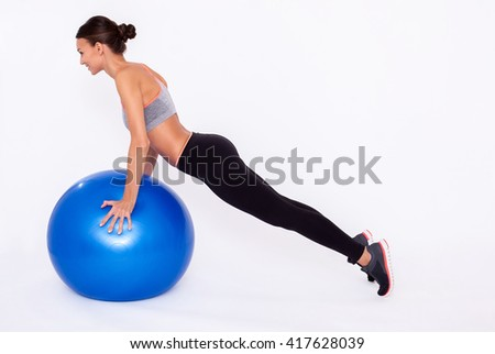Working my upper body Full length portrait of a young woman doing push ups with a fitness ball and balancing over white isolated background. - stock photo