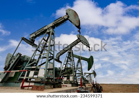 Working oil pump jacks on a oil field  - stock photo