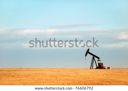 Working oil pump on Nebraska Great Plains - stock photo