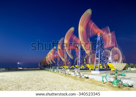 working oil-rigs on oilfield day and night - stock photo
