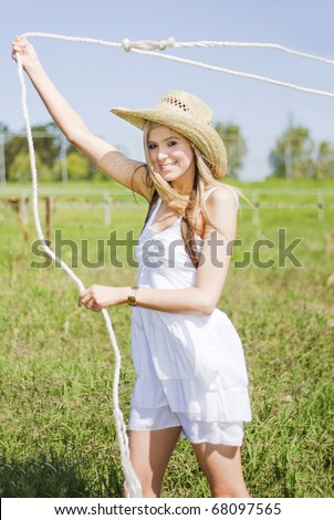 Working On A Green Pastoral Landscape A Farming Woman Swings A Rope Above Her Head To Catch A Stray Farm Animal - stock photo