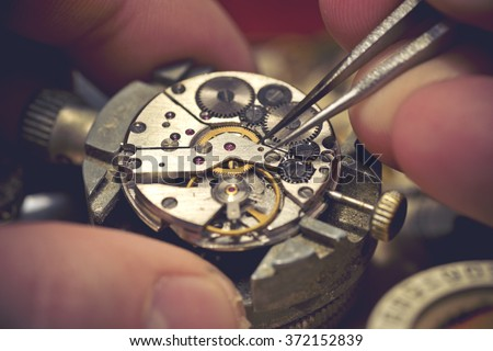 Working On A Mechanical Watch. A watch makers work top. The inside workings of a vintage mechanical watch. - stock photo