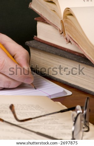 Working on a research paper with a pile of open books - stock photo