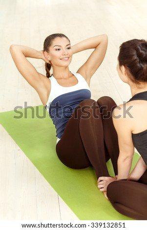 Working on abs. Vertical portrait of a beautiful woman doing abs exercise with her friend helping her holding her legs - stock photo