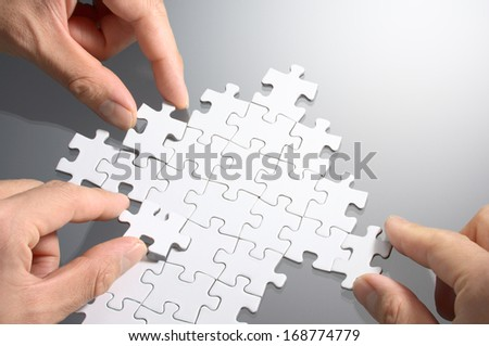 Working on an arrow shaped jigsaw puzzle. Concept image of making growth strategy.  - stock photo