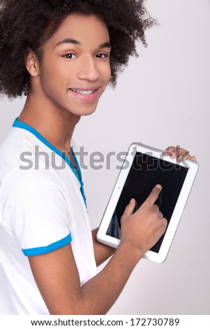 Working on digital tablet. Rear view of cheerful African teenager working on digital tablet and looking over shoulder while standing isolated on grey background