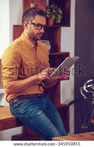 Working on his new tablet. Handsome young man working on digital tablet while standing near his working place in office - stock photo