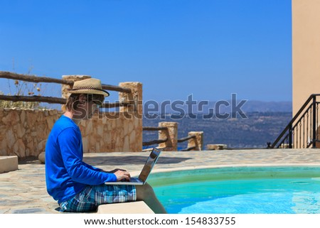 working on laptop at the pool, work on holiday concept - stock photo
