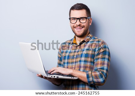 Working on laptop. Handsome young man working on laptop and smiling while standing against grey background - stock photo