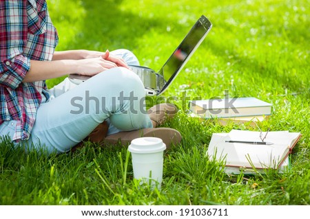 Working on laptop outdoors. Cropped image of female student working on laptop while sitting in a park with books around her - stock photo