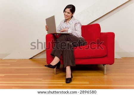 Working on laptop while sitting in red chair.