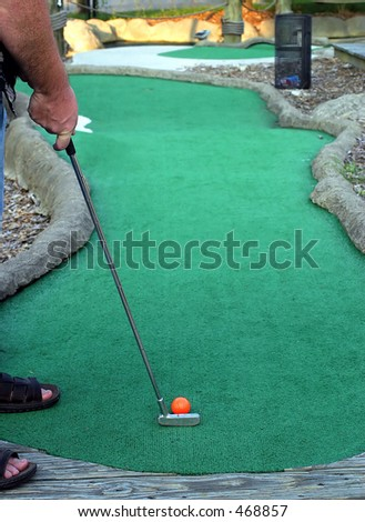 Working On My Putt.. a man playing miniature golf - stock photo