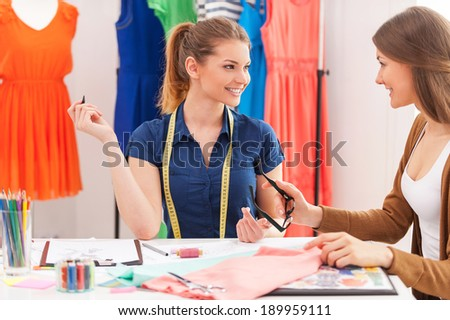 Working on new collection together. Two beautiful female designers talking and smiling while sitting at the working place  - stock photo