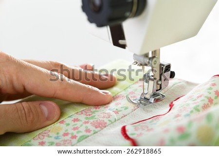 Working on sewing machine. Close look of hands and needle