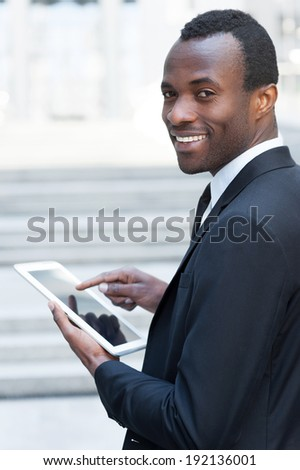 Working on tablet. Cheerful young African man in formal wear working on digital tablet and looking over shoulder while standing outdoors - stock photo