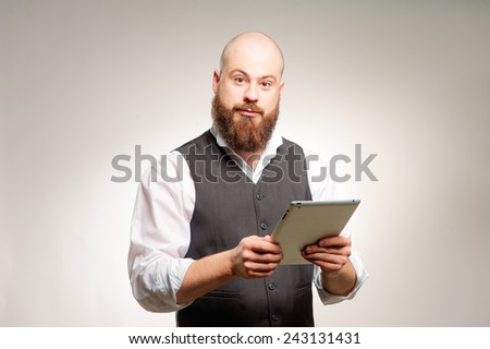 Working on tablet. Cheerful young caucasian bearded man working on digital tablet and looking at camera while standing against grey background. - stock photo