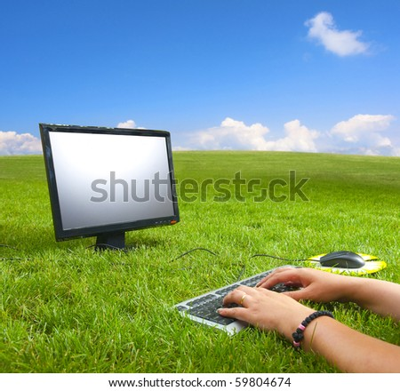 Working on the computer in the middle of the beautiful green meadow and under the blue sky on the sunny summer day. - stock photo