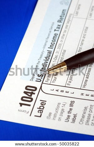 Working on the United States Income Tax 1040 isolated on blue - stock photo