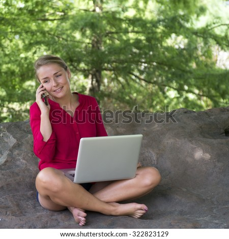 working outdoors - beautiful bare feet 20s girl smiling on cell phone with laptop on crossed legs in shape of trees sitting on giant rock,natural daylight