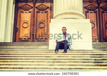 Working outside. Dressing in light gray blazer, black pants, brown leather shoes, a young black guy is sitting on stairs outside vintage style office building, hands holding laptop computer, thinking. - stock photo