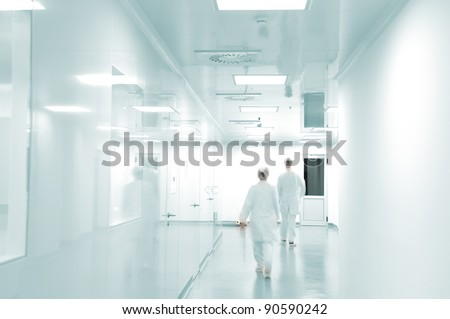 Working people with white uniforms walking in modern  factory environment - stock photo