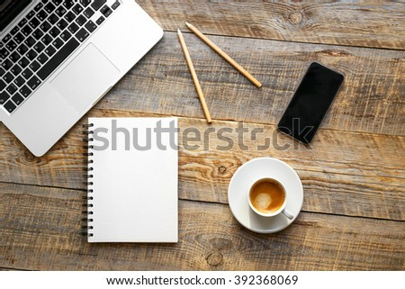 Working place with coffee cup, laptop, phone on wooden table - stock photo