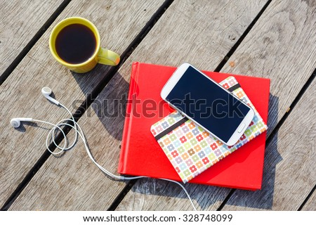 Working place with coffee cup, smartphone, headphones, stacked books on wooden background  - stock photo