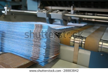 Working print machine with brochure pile - stock photo