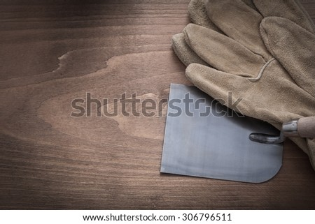 Working protective gloves and plastering trowel on vintage wooden background.