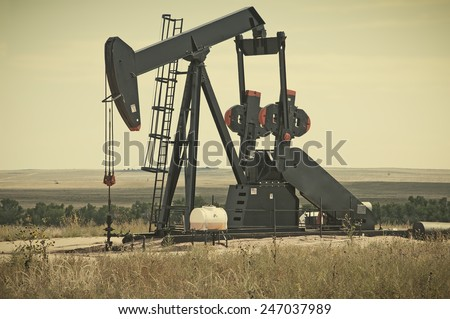 Working pump jack pulling crude oil out of an oil well in Colorado, USA. Retro instagram look.