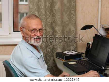 working senior with laptop computer at home - stock photo