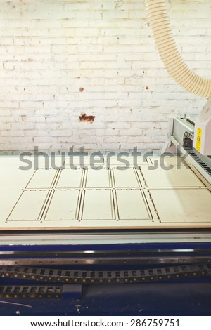 Working table of CNC wood router machine, white painted brick wall with a hole and flexible ventilation duct pipe from a machine. Router table with etching on product deck and belt drive above it - stock photo