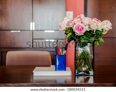 Working table with vase of roses in modern room - stock photo