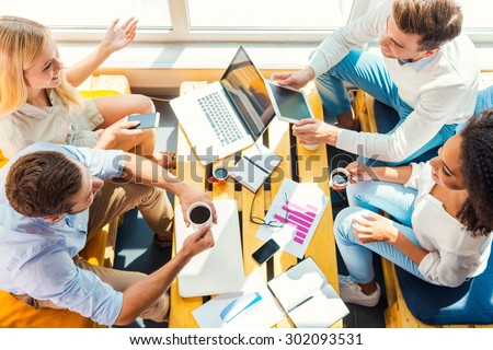 Working together for better results. Top view of four happy young people working together while sitting at the wooden desk in office - stock photo