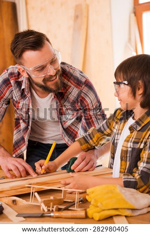 Working together. Smiling young male carpenter and his son looking at each other while working in workshop - stock photo