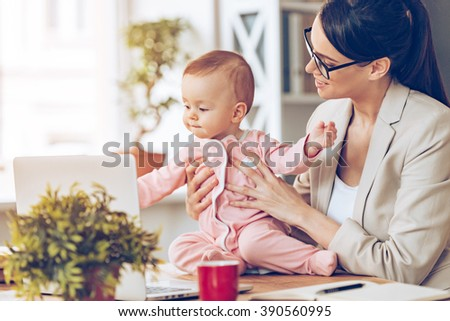 Working together with joy. Cheerful young beautiful businesswoman looking at her baby girl with smile while sitting at her working place - stock photo
