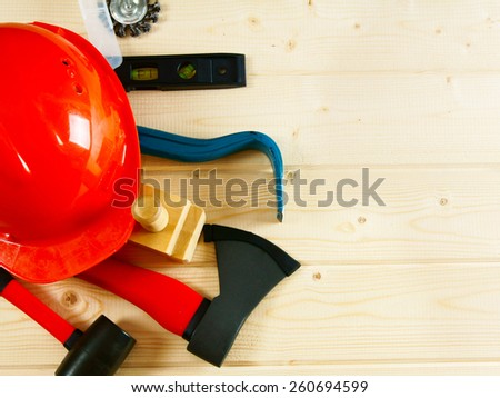 Working tools. A helmet, mount, an axe, a plane and other tool on a wooden background. - stock photo
