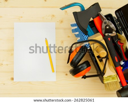 Working tools. A sheet of paper with a pencil and tools in a box on a wooden background. - stock photo