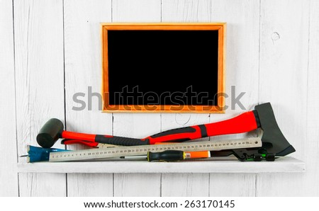 Working tools and frame. On a white, wooden background.
